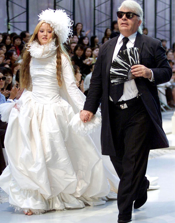 TOKYO, JAPAN:  German designer Karl Lagerfeld (R) of Chanel leads Japanese model Devon Aoki wearing a wedding dress during the autumn/winter 2000-2001 Chanel collection in Tokyo 12 May 2000. (ELECTRONIC IMAGE)  AFP PHOTO/Toru YAMANAKA (Photo credit should read TORU YAMANAKA/AFP/Getty Images)