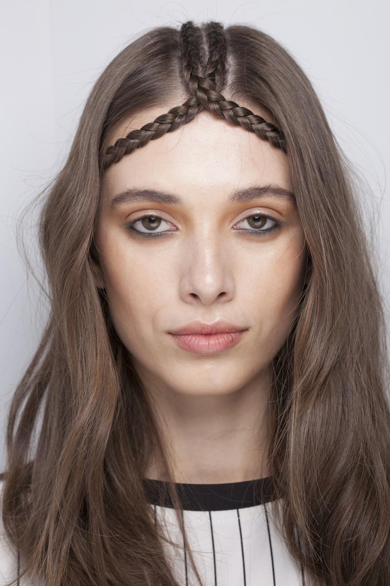 As tranças cruzadas no centro da cabeça fazem as vezes de acessório, mais do que de penteado no cabelo