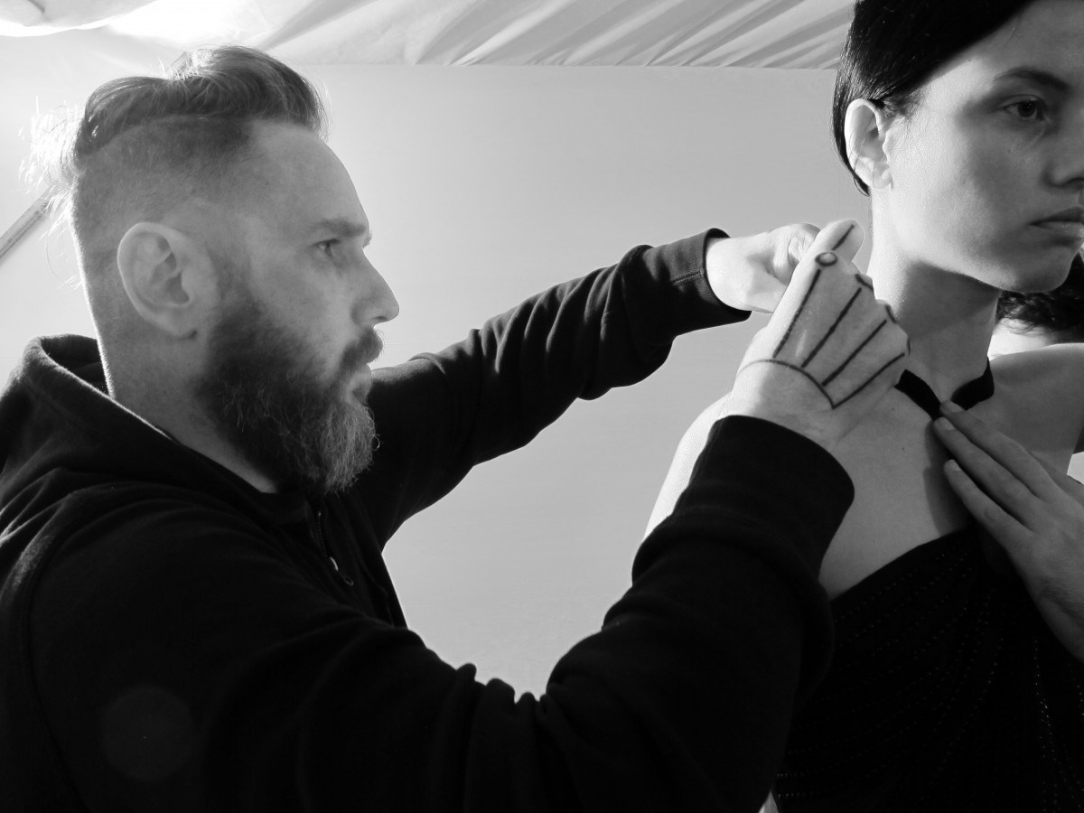 Alexandre Herchcovitch ajusta a roupa na modelo Isis Bataglia ©Jackson Araujo