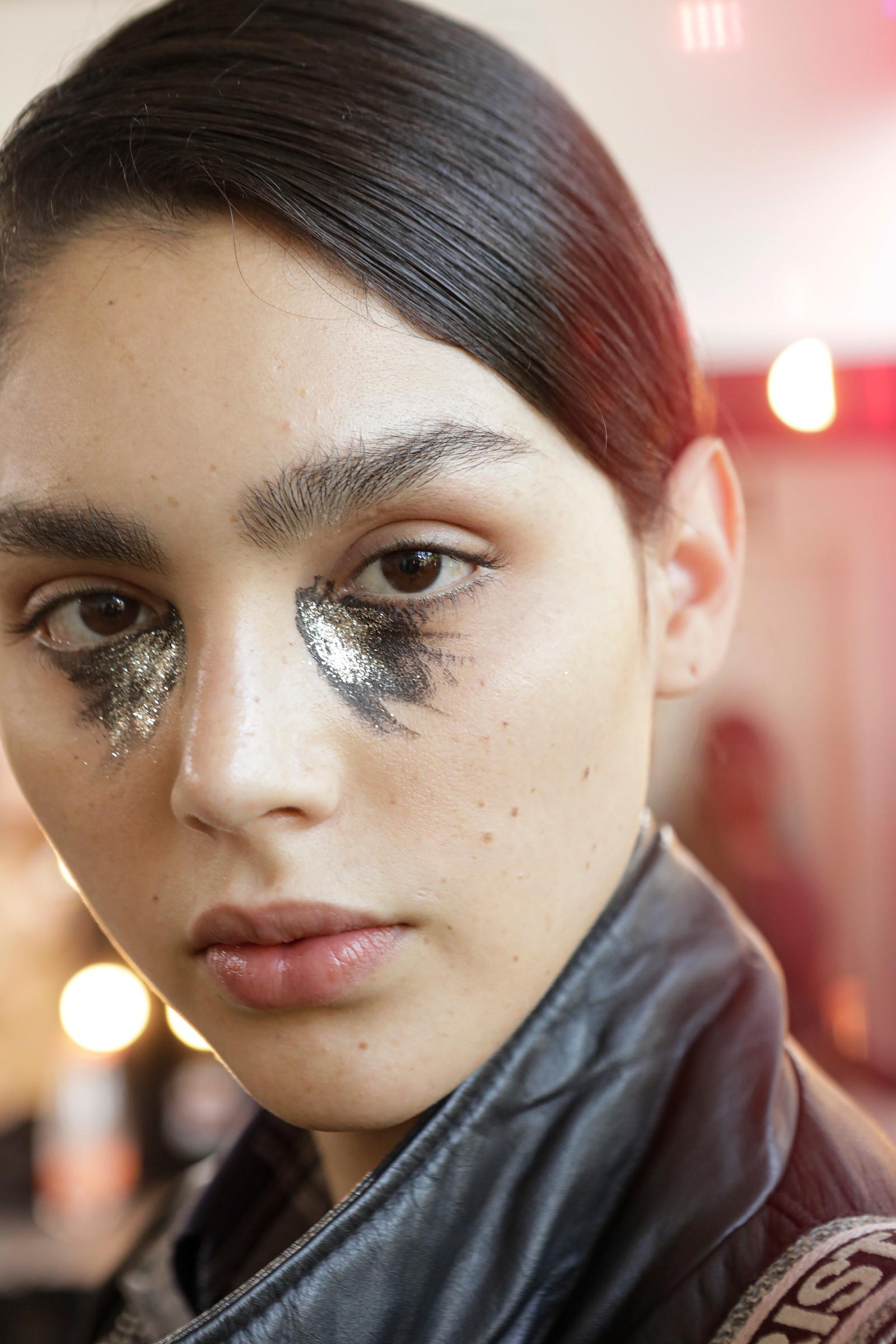 Manchas heterogêneas em preto e glitter prateado pintavam a parte debaixo dos olhos na beleza de Laura Prestes para João Pimenta / FOTOSITE